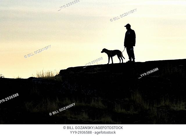 Silhouette of a man and his dog at Cattle Point, Uplands Park, Oak Bay, Victoria, Vancouver Island, British Columbia, Canada