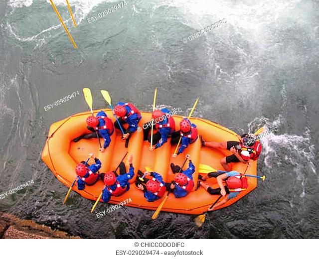 Daredevil athletes during the descent with the boat along an impetuous torrent