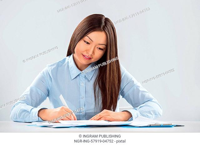 Closeup portrait of a cheerful young businesswoman with a pen in her hand