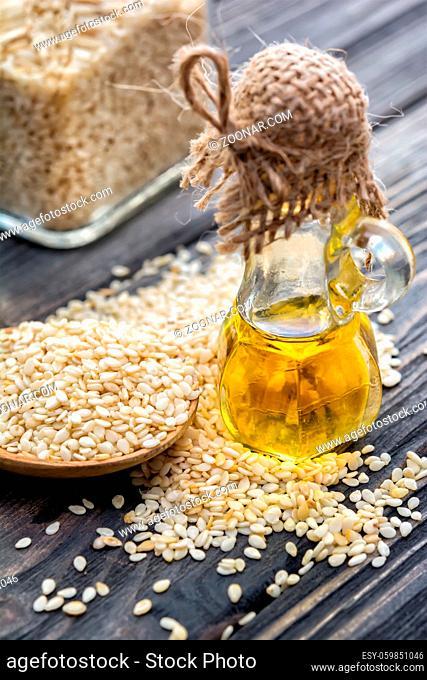 Sesam oil in bottle, sesam seeds, spoon on wooden background