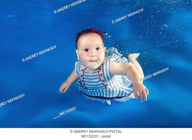 A little girl in a dress floats under waterin a swimming pool