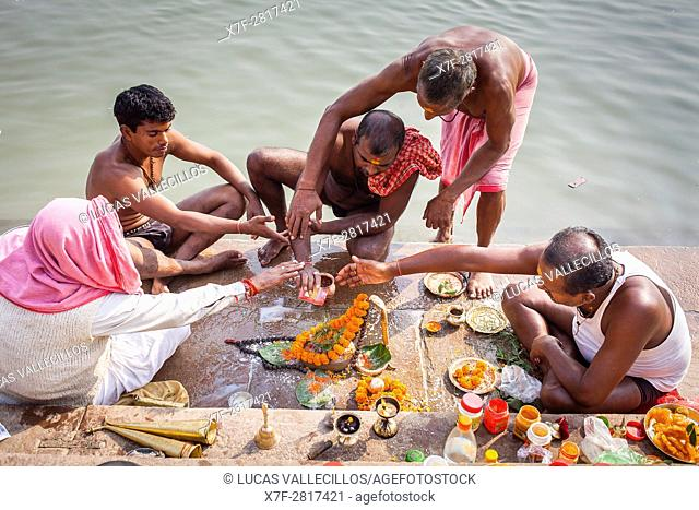 Pilgrims making a ritual offering and praying, ghats of Ganges river, Varanasi, Uttar Pradesh, India
