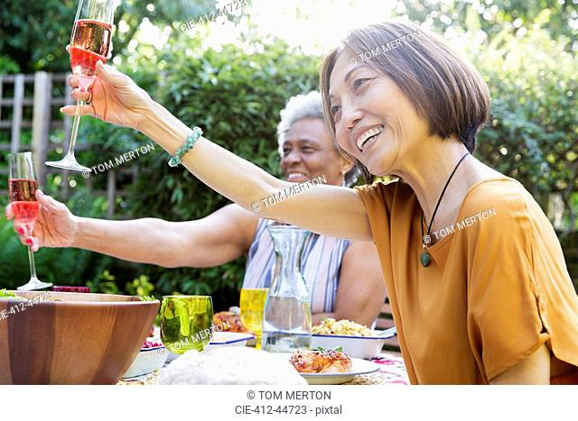 Happy active senior women toasting rose wine at garden party