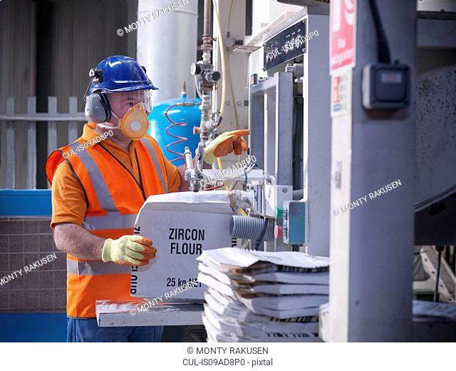 Worker in protective clothing filling zircon flour bags in mill