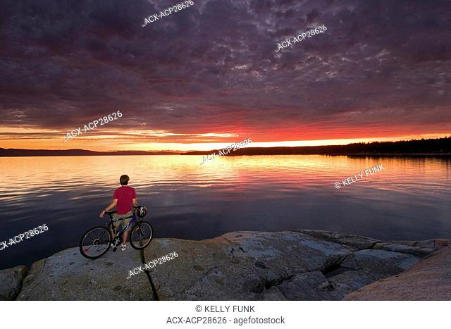 A lone biker admires a beautiful evening on the Pacific ocean, near Powell River, on the Sunshine coast of the Vancouver coast and mountain region of British...