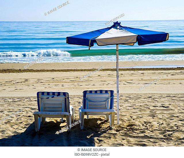 Sunlounger and parasol on beach, Benidorm, Costa Blanca, Spain