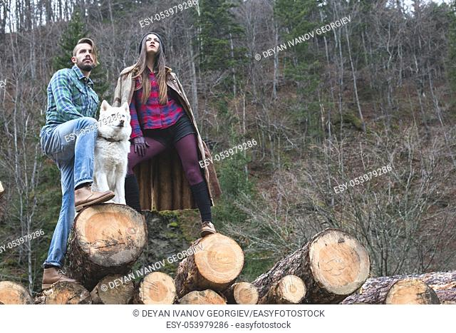 Young woman and men on wood logs in the forest. White dog