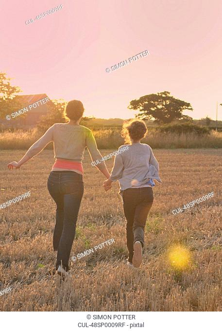 Mother and daughter running in field