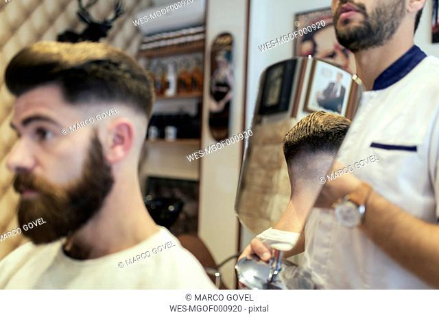 Customer checking his hairstyle in a barber shop