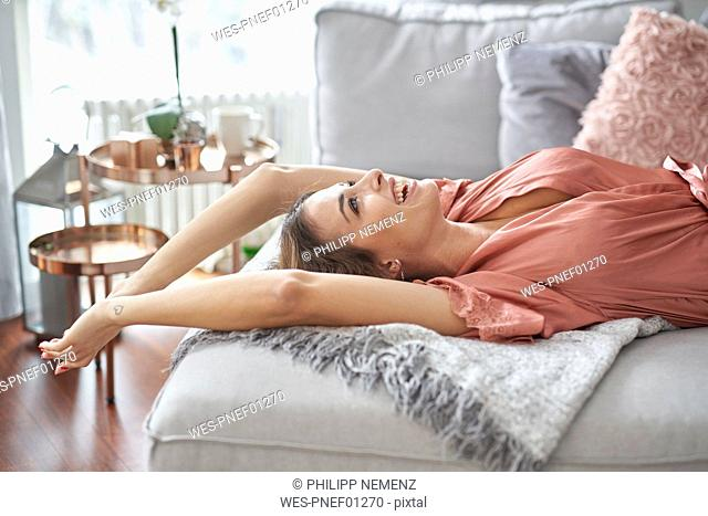 Laughing young woman in dressing gown lying in bed