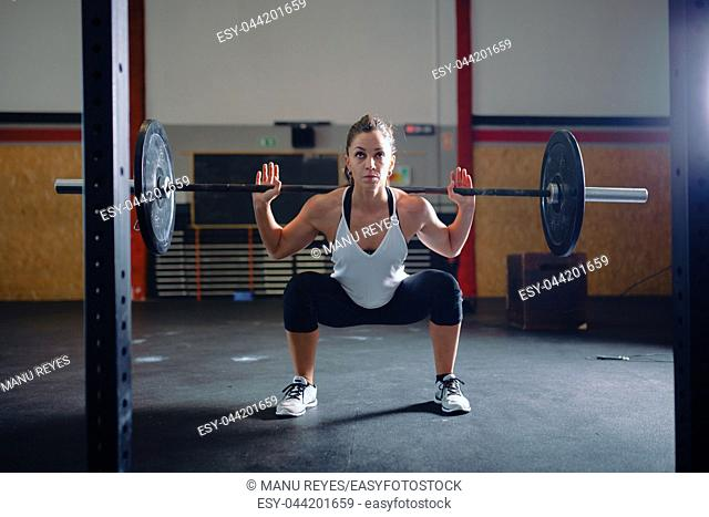 Athletic brunette young woman doing some weightlifting exercises