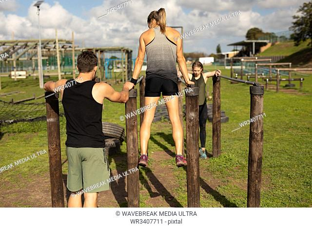 Rear view of a young Caucasian woman and a young Caucasian man using parallel bars at an outdoor gym during a bootcamp training session