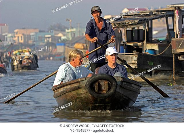Two visitors being paddled around Cai Ran floating market near Can Tho Vietnam