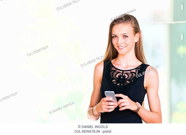 Young woman holding smartphone looking at camera smiling