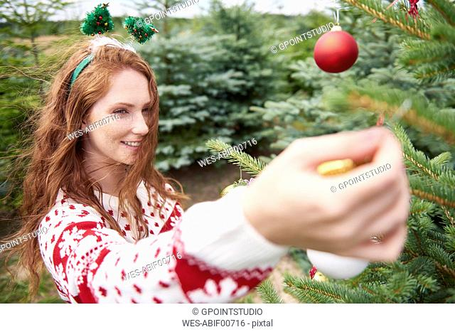 Redheaded young woman decorating Christmas tree outdoors