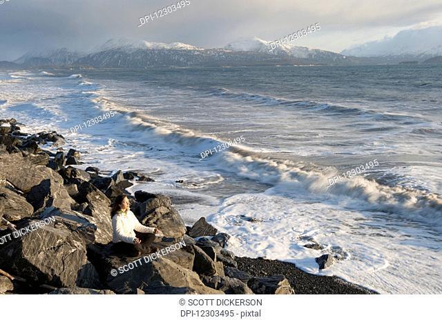 Woman practicing meditation on a rocky beach, Homer Spit, Southcentral Alaska