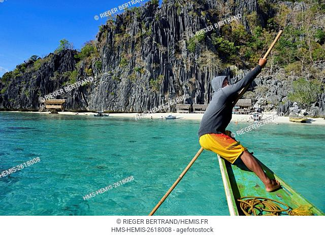 Philippines, Calamian Islands in northern Palawan, Coron Island Natural Biotic Area, Banul Beach under giant walls of limestone cliffs, boatman