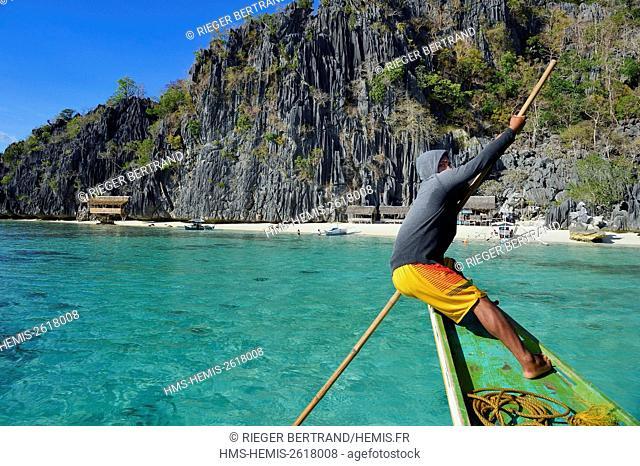 Philippines, Calamian Islands in northern Palawan, Coron Island Natural Biotic Area, Banul Beach under giant walls of limestone cliffs, boatman