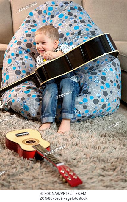Little happy boy plays the guitar hits