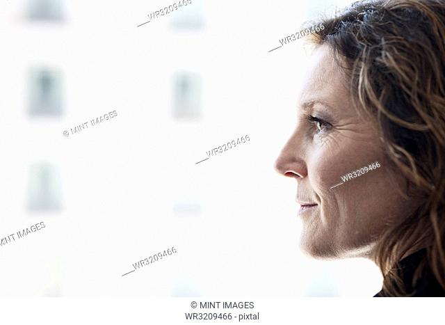 Caucasian business woman looking out the window of a conference centre lobby