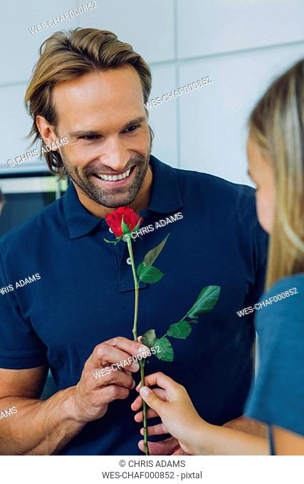 Smiling father and daughter with red rose
