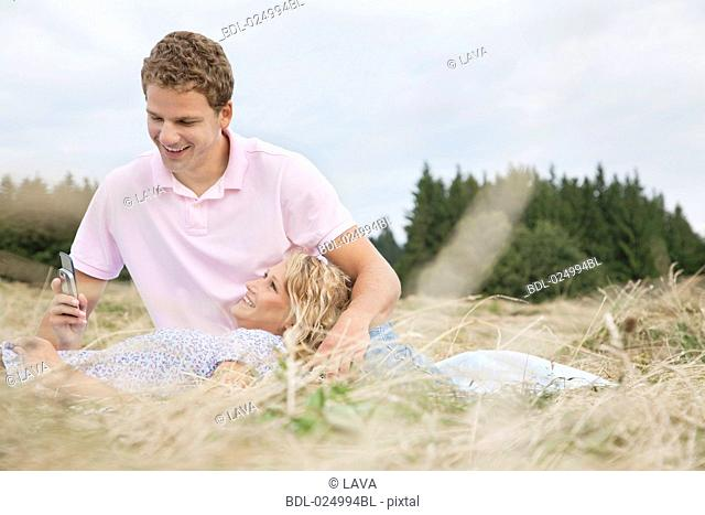 young couple in field man looking at display of mobile phone
