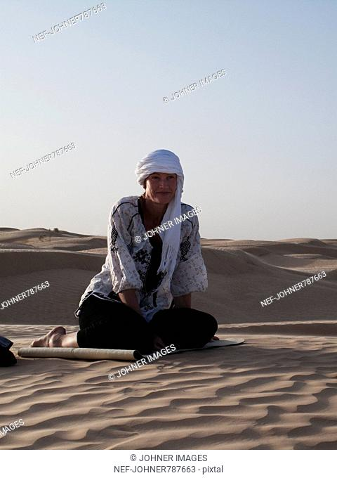 Woman relaxing in the desert, Tunisia