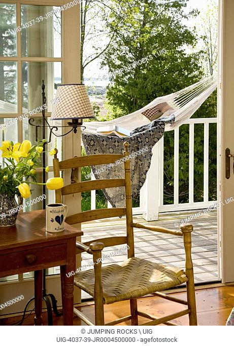 Period country chair next to wooden table in front of open door to patio with Hammock