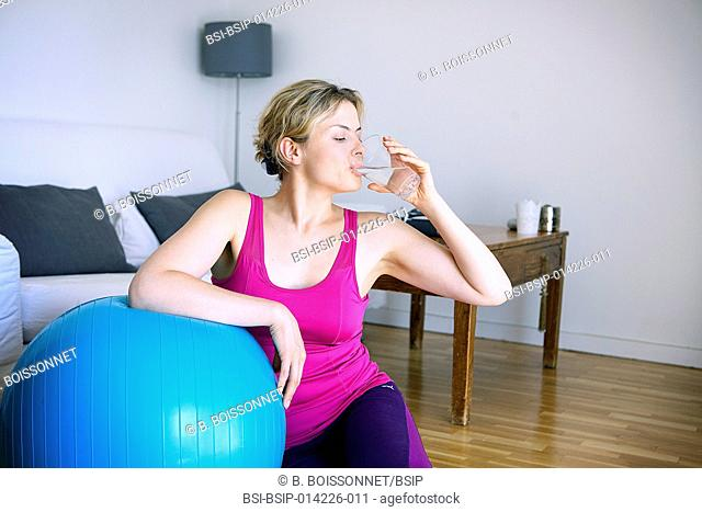 Woman drinking water after a gym session