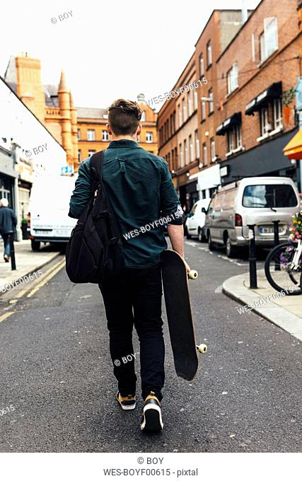 Ireland, Dublin, back view of young man with skateboard walking on the street