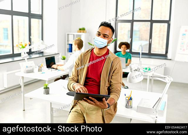indian man with tablet pc in face mask at office