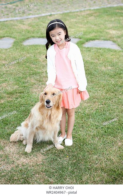 Girl standing with her dog on the grass at the yard of her house in Jeju