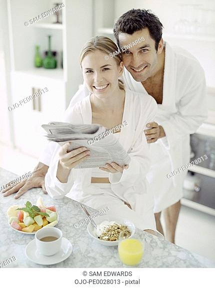 Man and woman in bathrobes with healthy breakfast reading newspaper