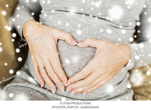 pregnant woman making heart gesture on her belly