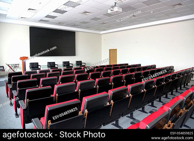 Rows of red seats in an empty room for presentations, press conferences and seminars