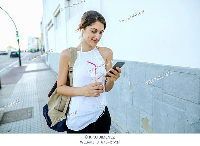 Young woman with cell phone and smoothie walking down the street
