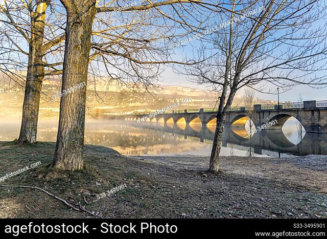 Long bridge over The Linares del Arroyo reservoir and Maderuelo village on a foggy morning. Segovia. Spain. Europe