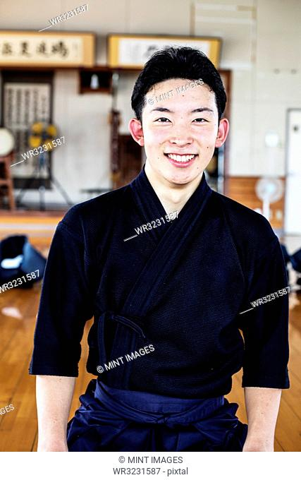 Male Japanese Kendo fighter standing in a gym, smiling at camera