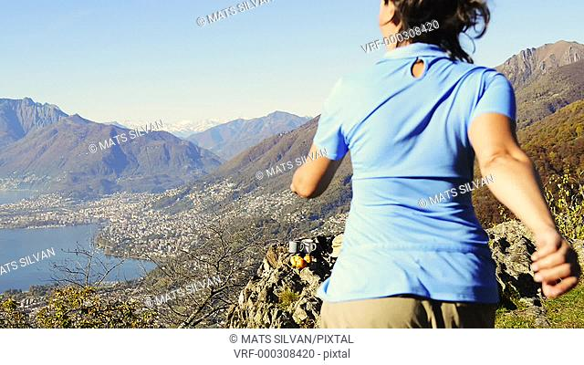 Woman standing on Mountain Top with Arms Outstretched in Ticino, Switzerland