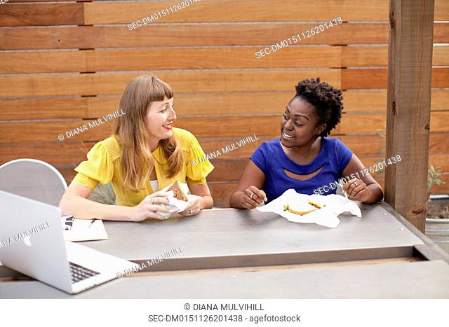 Female coworkers eating sandwiches