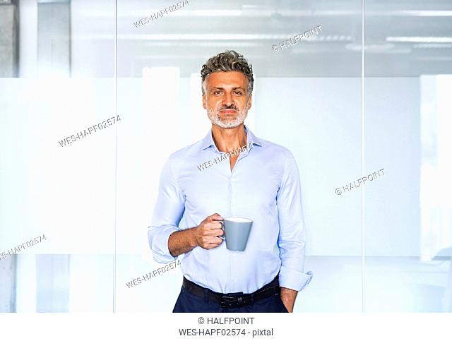 Portrait of confident mature businessman holding coffee mug