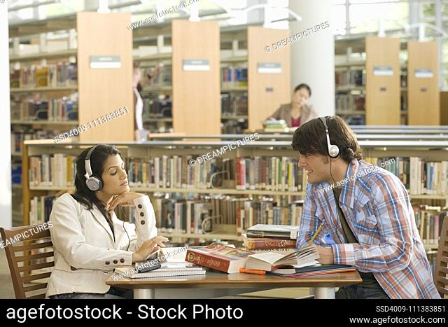 Multi-ethnic couple studying in library