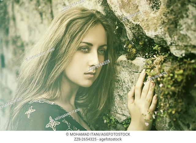 Attractive young woman leaning against the wall looking away with a contemplative expression