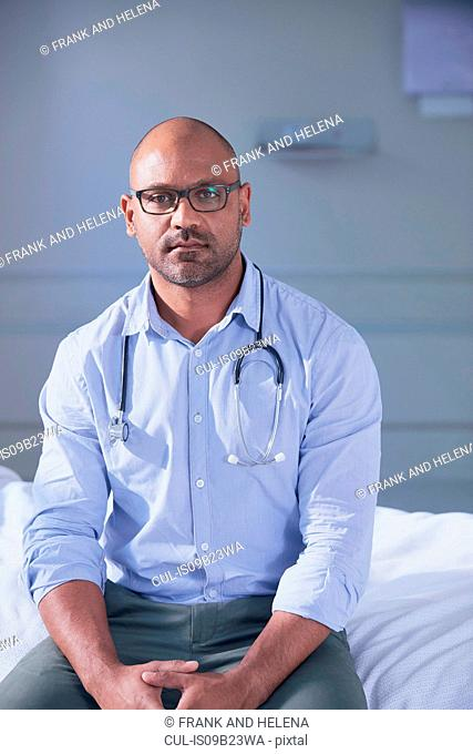 Portrait of mature male doctor sitting on hospital bed