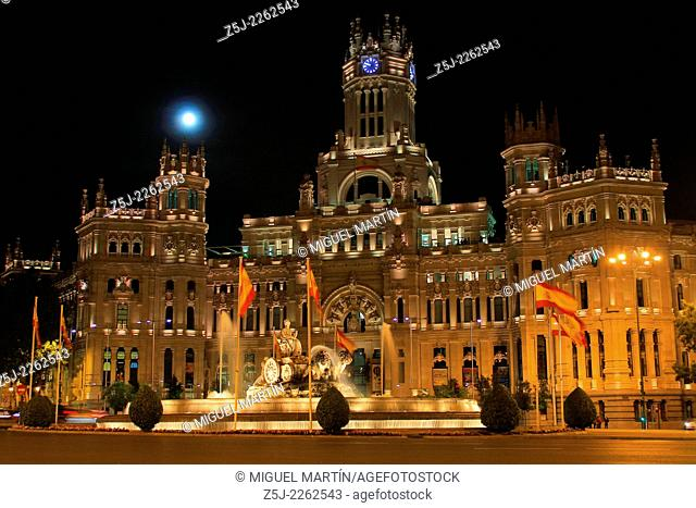 The full Moon rises over the Palacio de Cibeles (1919) built by Antonio Palacios to house the headquarters of the postal service until 2007 when it became the...