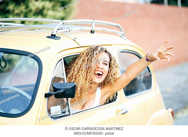 Portrait of happy blond woman leaning out of window of classic car showing victory sign