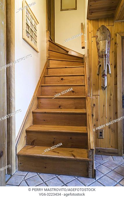 Pinewood staircase leading to upper floor inside an old circa 1752 Canadiana style fieldstone house