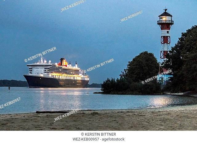 Germany, Hamburg, Hamburg-Rissen, Lighthouse Wittenbergen, Cruise ship Queen Mary 2 on Elbe river at blue hour