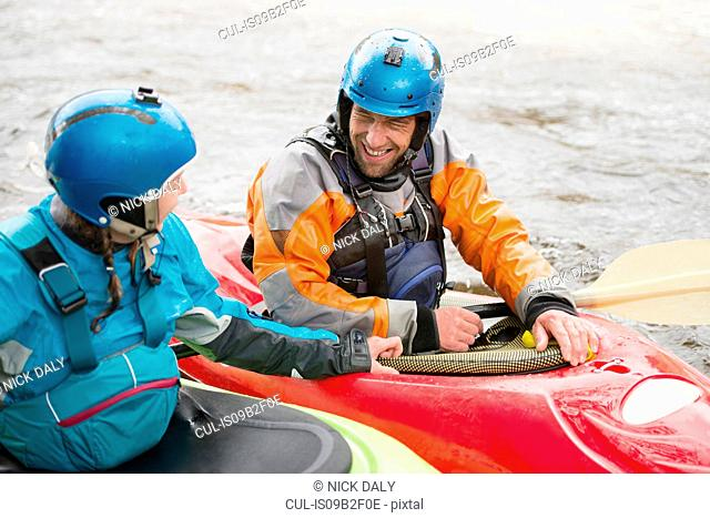 Male and female kayakers talking on River Dee
