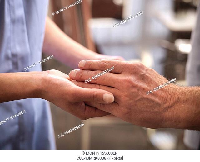 Nurse examining older mans hands